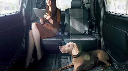 ミニバンの車内でくつろぐ女性と犬